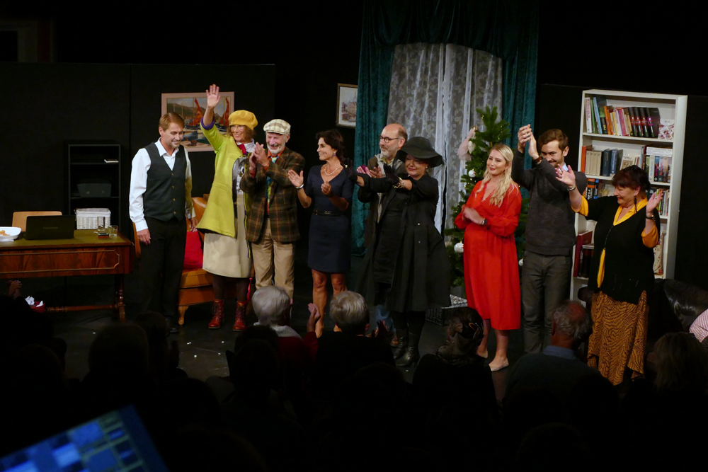 Viele Schauspieler stehen klatschend bei einer Schlussszene auf der Bühne